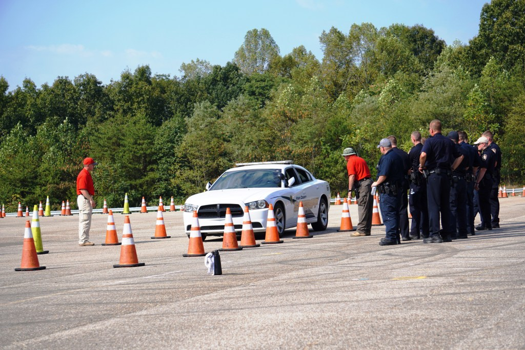 Instructor and officers standing on driving course with KCSO cruiser