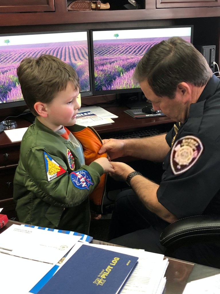 Sheriff at desk talking to small boy