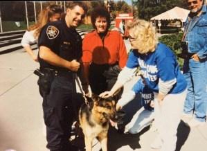 Older image of K9 officer letting civilians meet his dog
