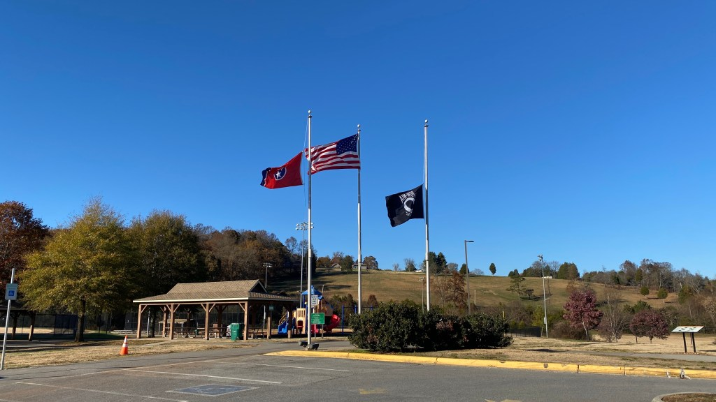American, Tennessee, and POW flags near playground and covered tables