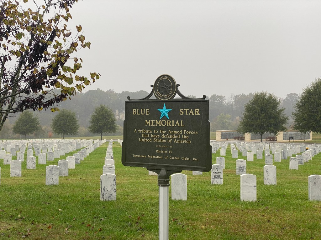 Blue Star Memorial sign with tombstones in background