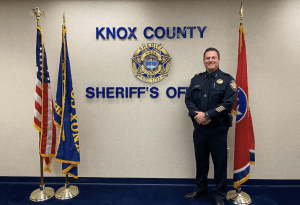 Chief Workman in uniform smiling next to KCSO wall logo and flags