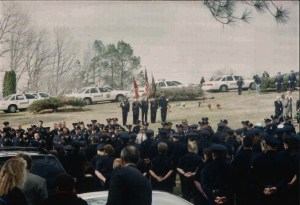 Officers standing at attention with flags at a funeral