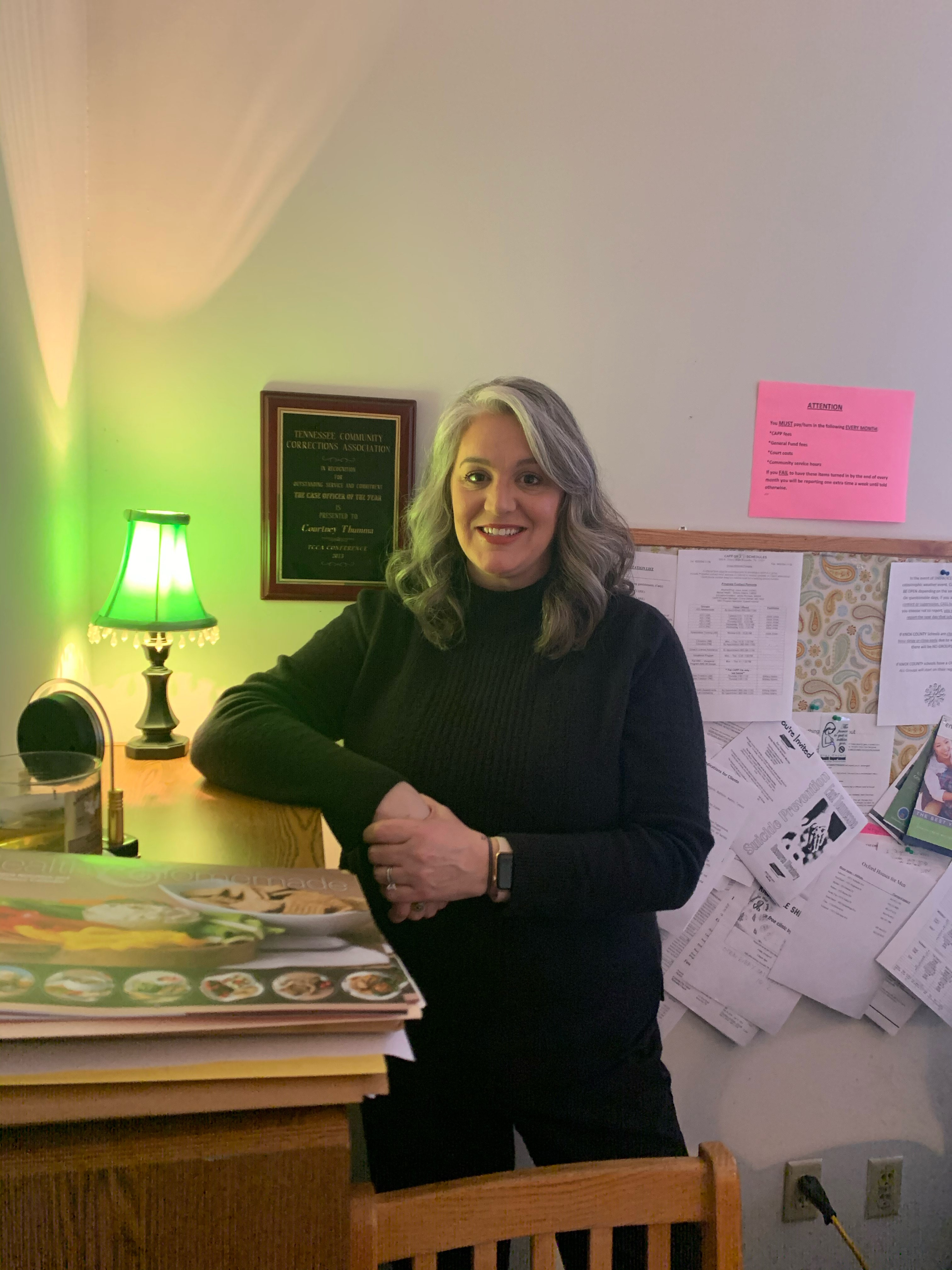 Courtney Thumma standing next to bookshelf
