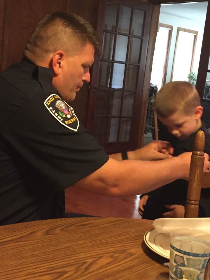 Chief Gibson helping small boy at a table