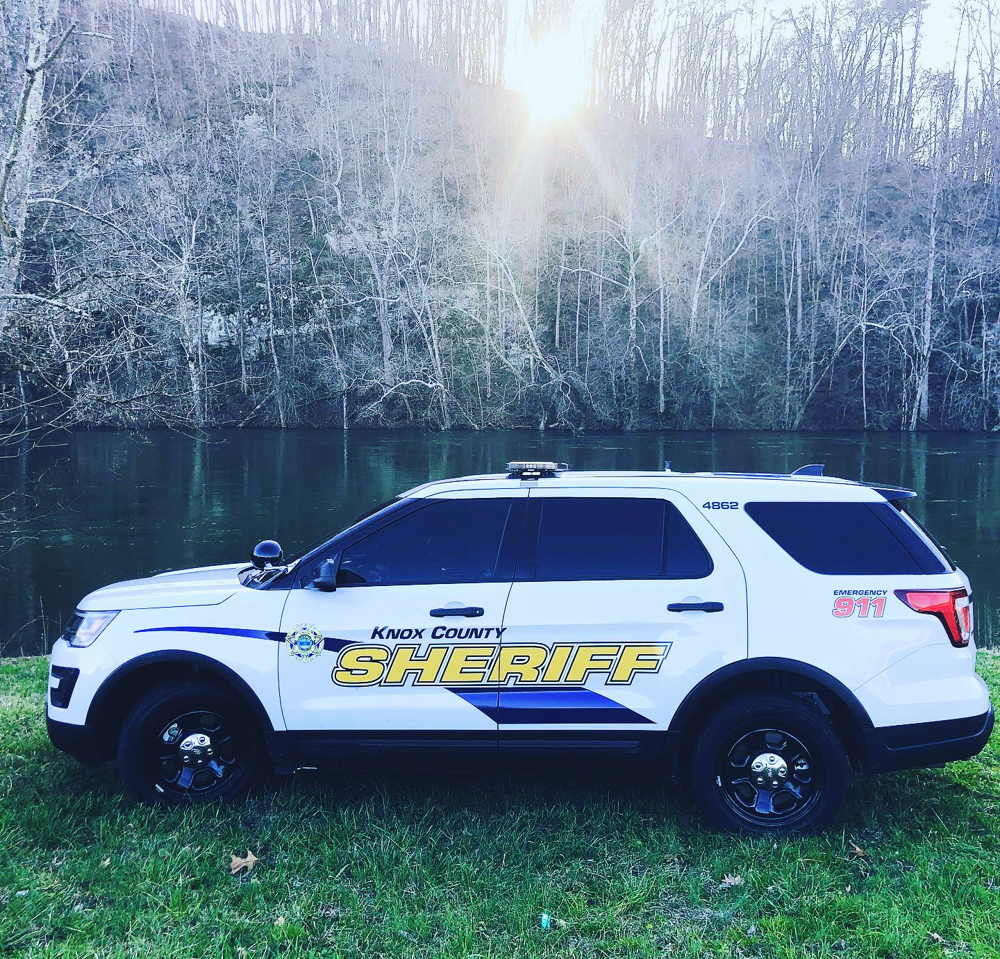 Sheriff Marked SUV parked on grass in front of lake