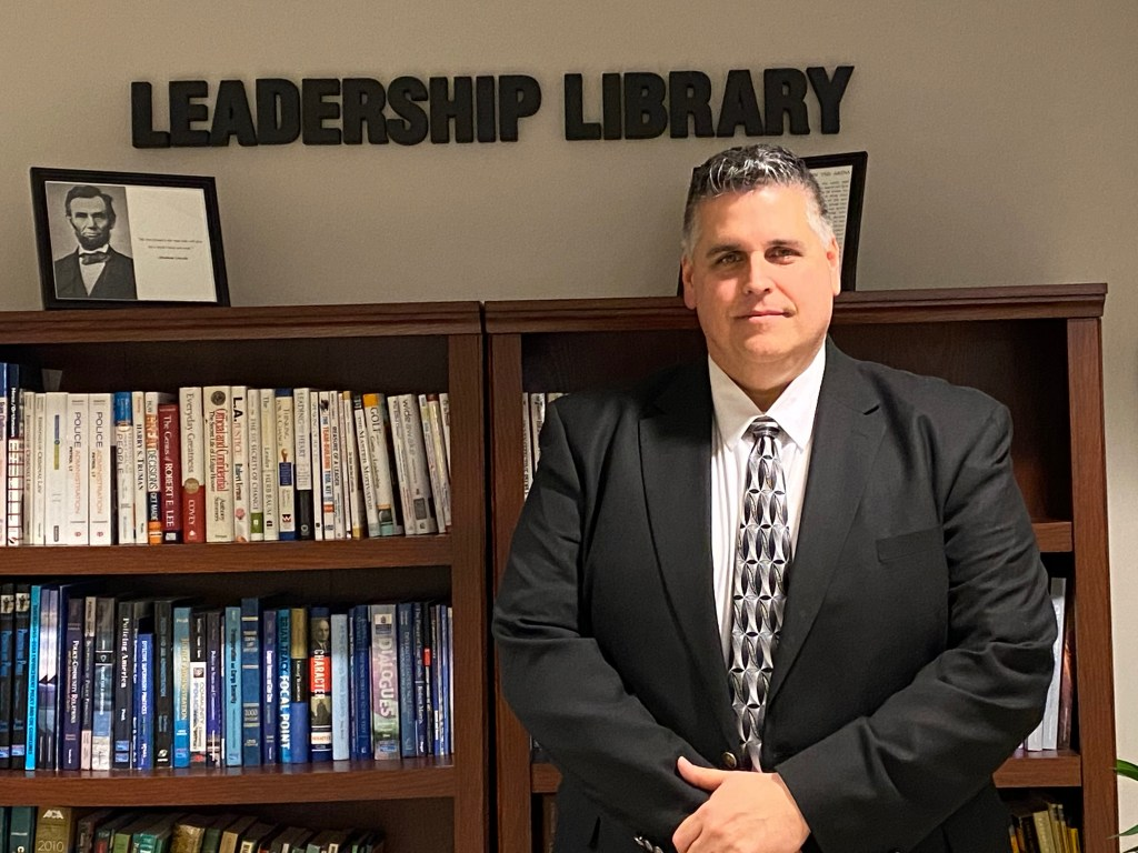 "Chief Steve Bravo, in suit, standing in front of bookcase of the ""Leadership Library"""