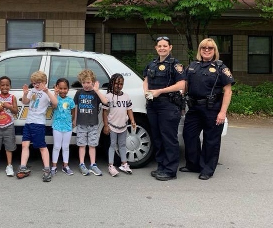 Two female deputies standing at rear of cruiser with children