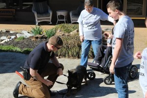 K9 and handler letting boy in wheelchair and man and woman meet the dog