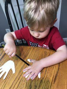 boy decorating hand cutouts