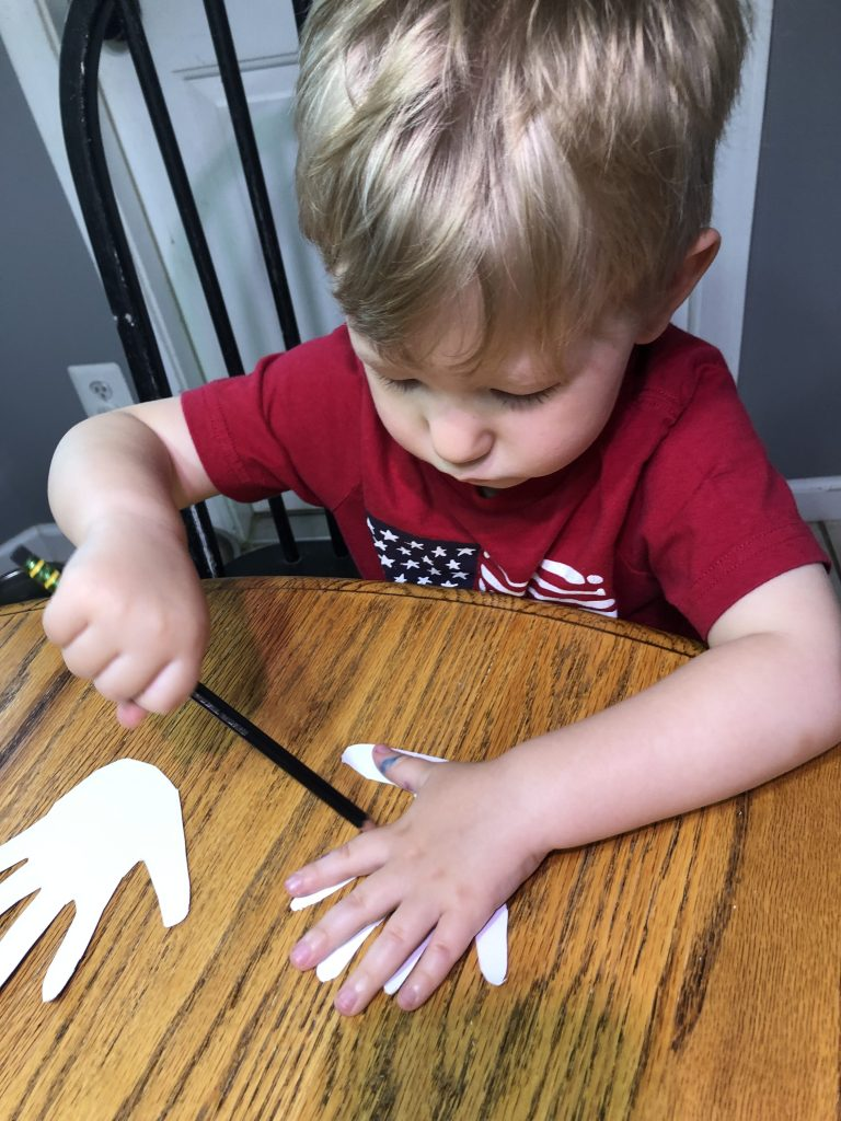 boy decorating hand cutouts