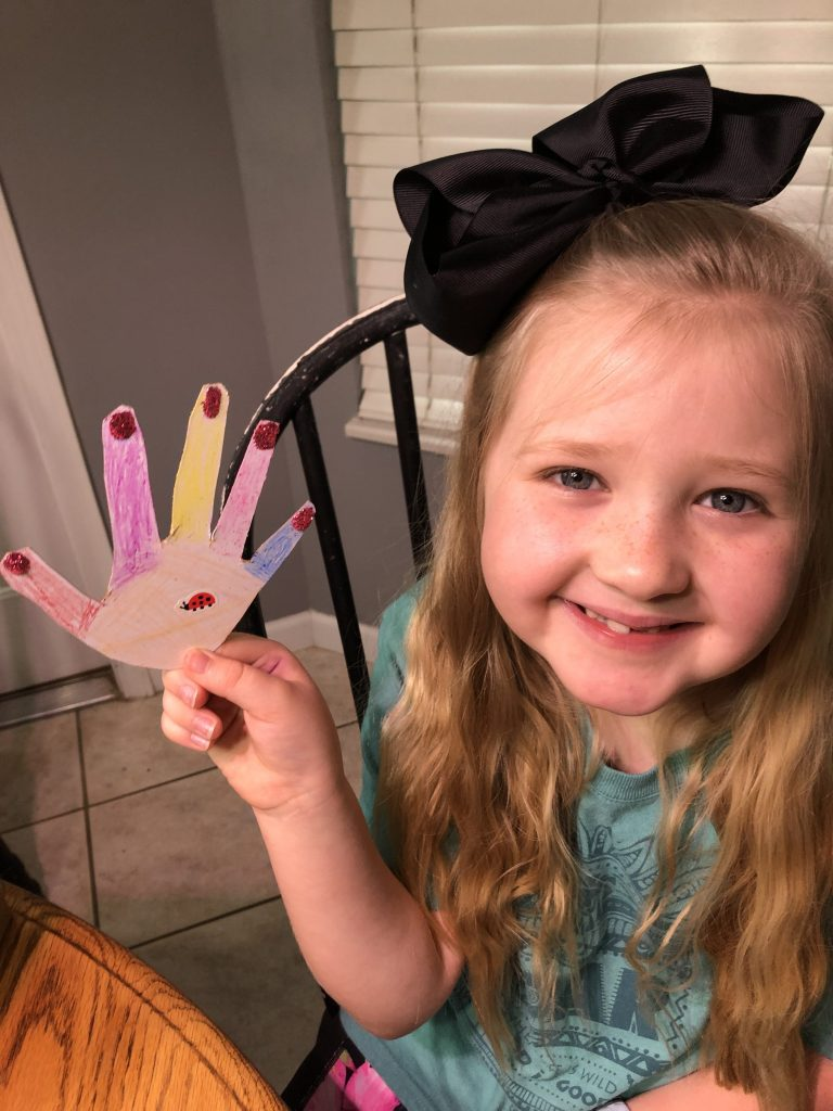 girl smiling and showing her colored hand cutout