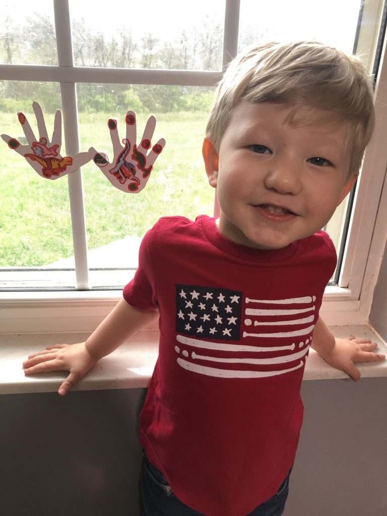 boy smiling with hand cutouts in window