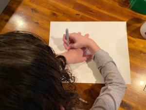 Child tracing hand on paper