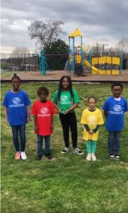 5 children wearing Boys & Girls club standing in playground smiling at camera