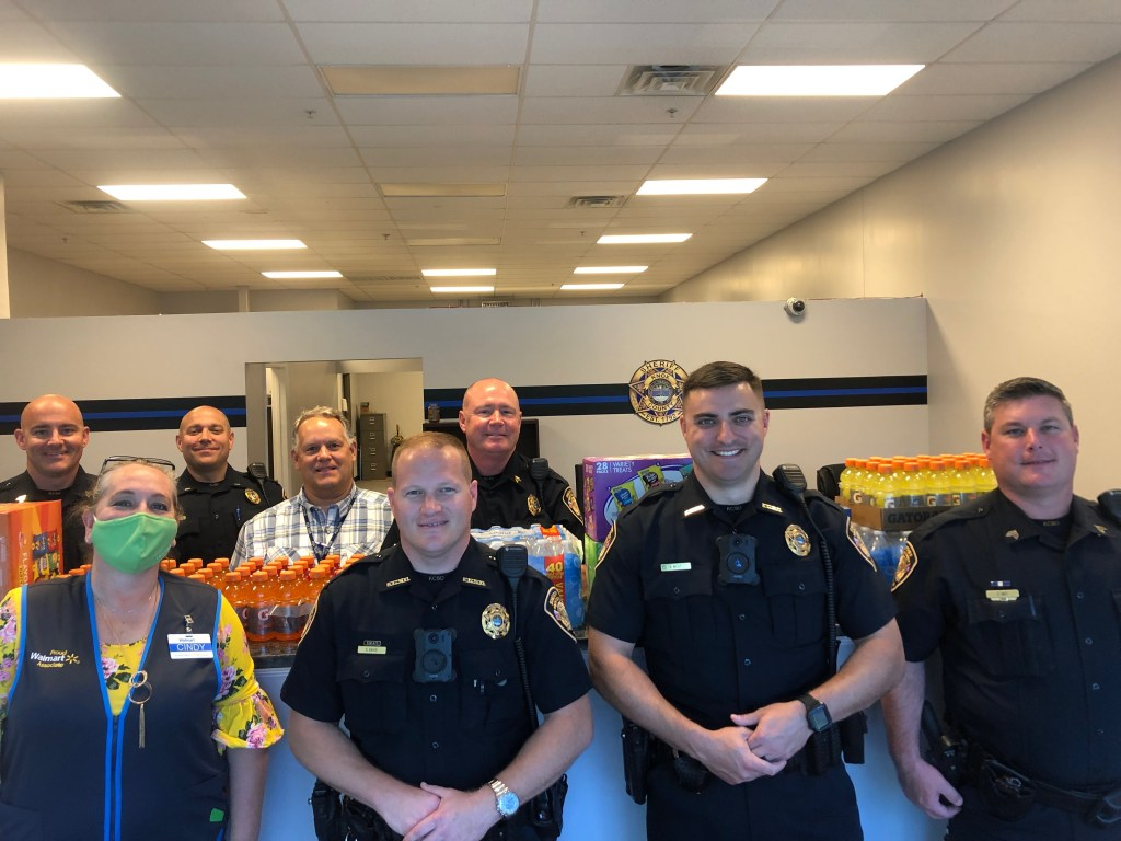 Officers and Walmart staff standing in front of donated supplies