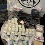 Narcotics, money, guns, on desk with KCSO badge overlay
