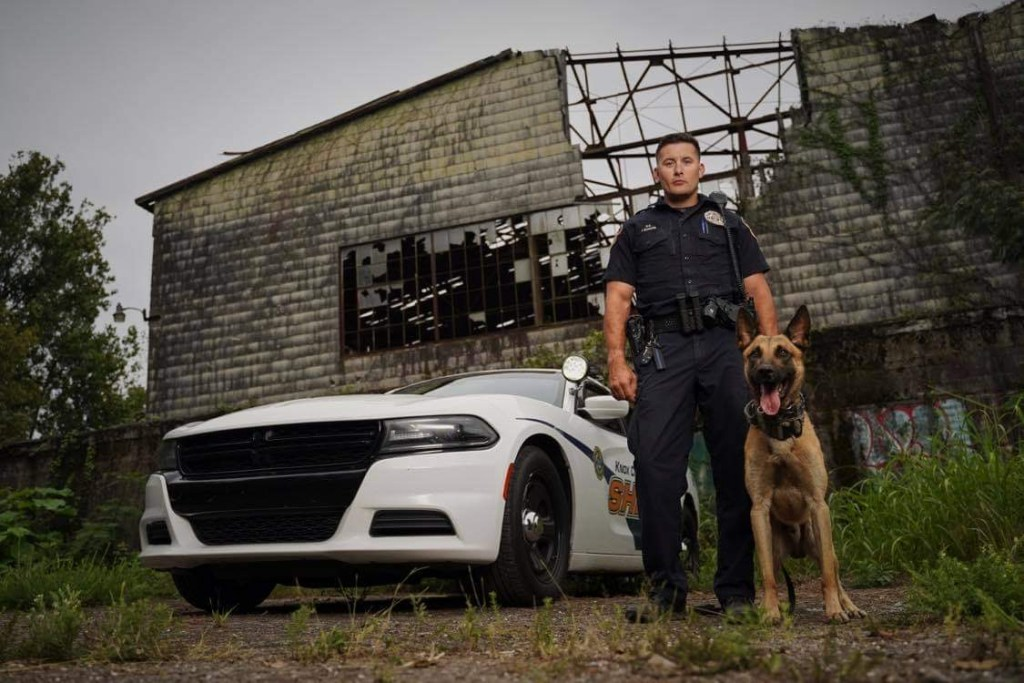 Officer and K9 standing next to cruiser