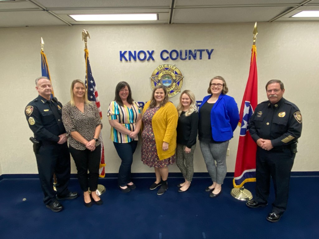 Sheriff and Chief Deputy standing with Support Services staff between flags and KCSO emblem