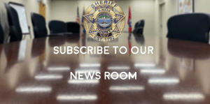 """Conference table and chairs with badge and """"Subscribe to our newsroom"""""""