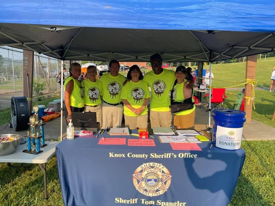 Officers at mud volleyball stand