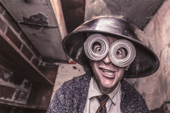 A man in an abandoned building wearing a suit and tie, a colander, and silly glasses, making a silly face.