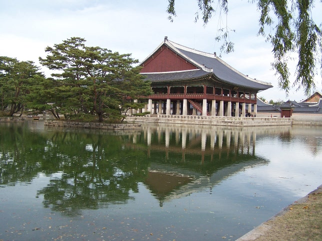 A portion of Gyeongbukgung palace reflected in the water on a sunny autumn day.
