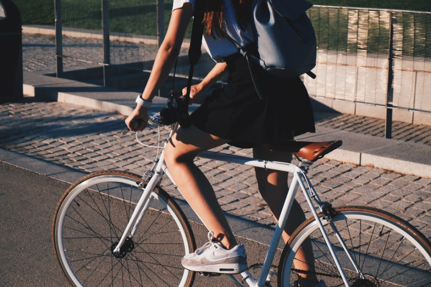 A white woman in a black sirt and a white t-shirt riding a vintage light blue bicycle down a sidewalk on a sunny day.