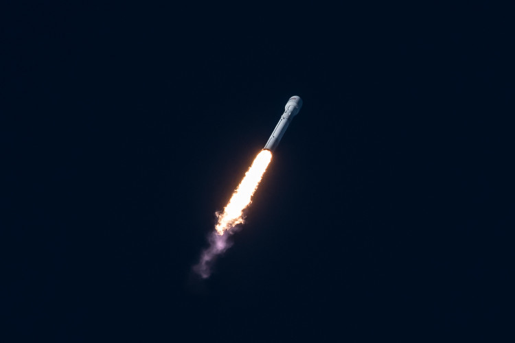 The SpaceX rocket taking off against a dark blue sky.