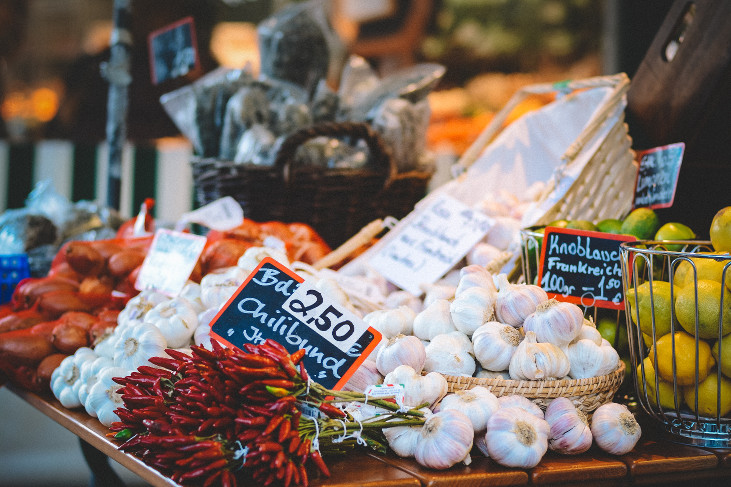 Garlic, chili peppers, and other foodstuffs in baskets on a market table.