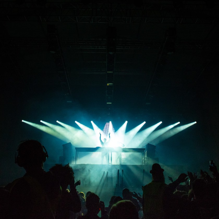 A dozen blazing spotlights focusing on a distant figure on a stage, framed by darkness and dark silhouettes.