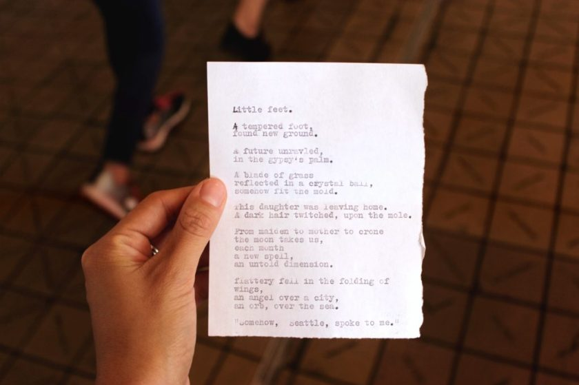 A Caucasian hand holding a small sheet of paper with a typewritten poem.