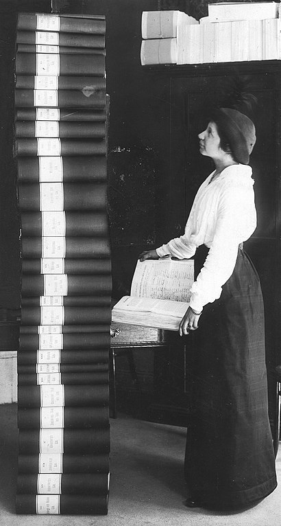 Elin Wägner in front of the 351,454 signatures collected to support women's right to vote, a stack of binders half a meter taller than herself.