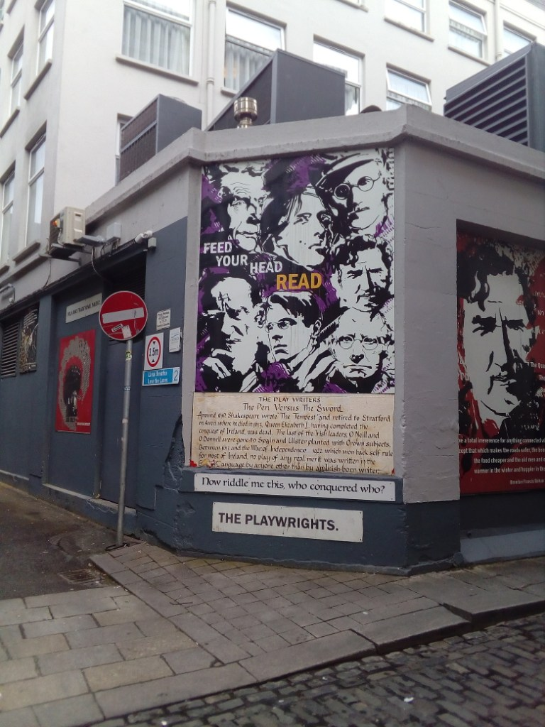 """Street art with high-contrast black and white portraits of Irish writers on a purple background, with text that says """"Feed your head: read."""""""