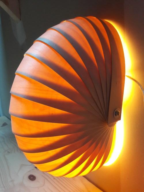 lampe à poser en lames de bois fin, forme demi-rond en lames de bois; lumière intérieure-effets de superposition, jaune et brun. Ambiance chaleureuse