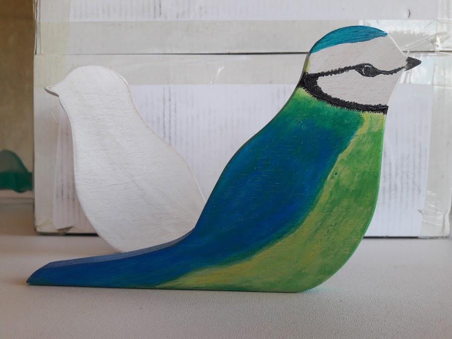 découpe de bois, mésange,peinte,couleurs,bleu,vert,jaune ou patine grise et beige. S'utilise comme cale-porte. Léger et décoration.