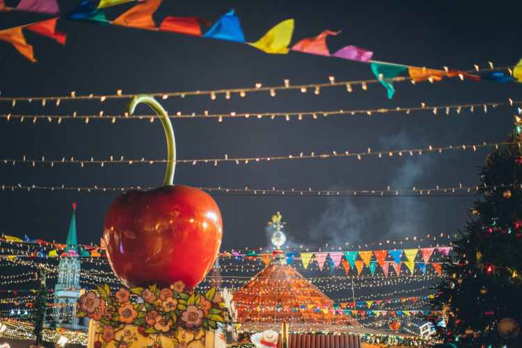 giant decorative apple on roof of stall on colorful new year fairground in downtown at night