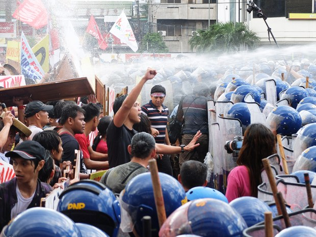 Anakbayan leader Vencer Crisostomo raises fist in defiance of another push by the police.