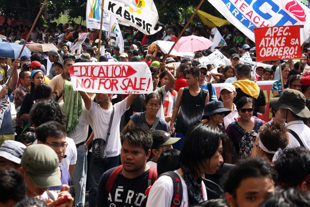 An activist teacher displays his opposition to the APEC summit happening a short distance away.