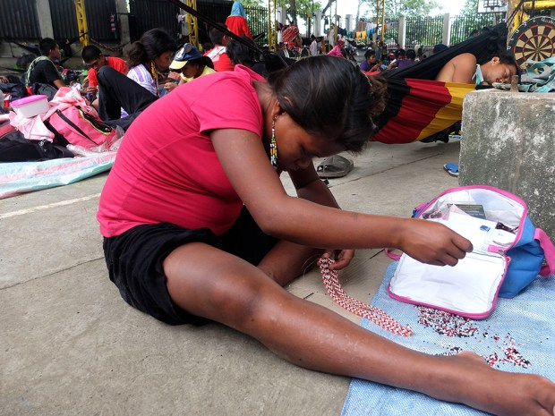 Deep in concentration, another Manobo woman finishes a necklace of white, black and red.