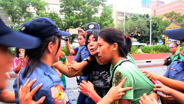 Injured and bleeding protesters being accosted by the police.