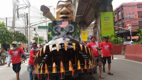 "Duterte effigy ""Dut-in-Boot"" being rolled to Mendiola to be burned by participants of Lakbay Magsasaka. (Photo by Kathy Yamzon)"