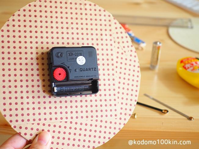 知育時計を作る おもちゃ時計の裏に折り紙を貼って時計を固定