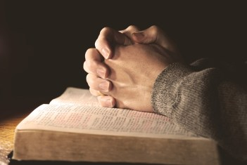 hands clasped on an open bible