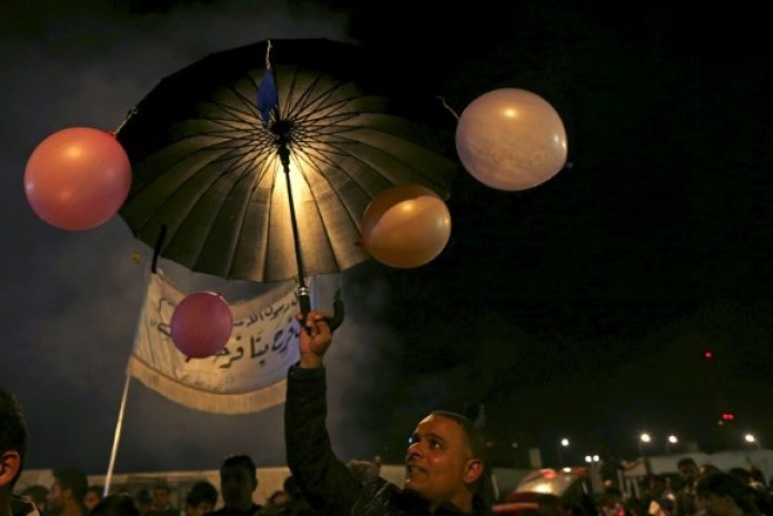 A man carries an umbrella decorated with balloons during a procession celebrating Mawlid in Benghazi, Libya. (Reuters)