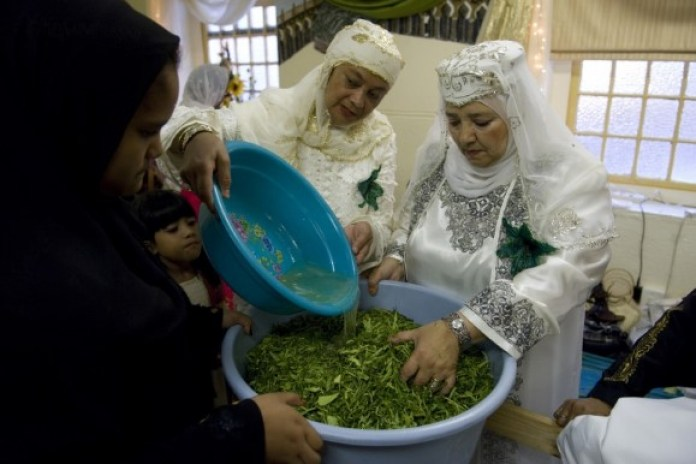 Keeping the tradition alive, Muslim women and children in Cape Town, South Africa, in their finest clothes cut lemon and orange tree leaves while reciting salutations upon the Prophet. (Getty Images)