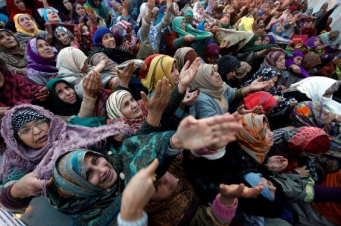 Women react upon seeing a relic believed to be a hair from the beard of Prophet Muhammad, on display at the Hazratbal shrine in Srinagar, Kashmir. (Reuters)