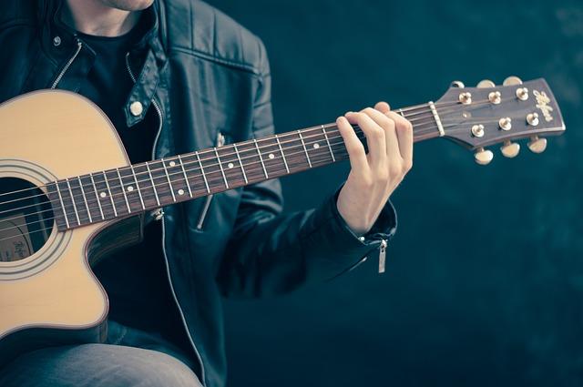 ギターを弾くジャケットの男性