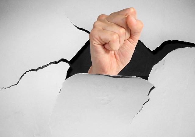 壁を突き破る拳の画像