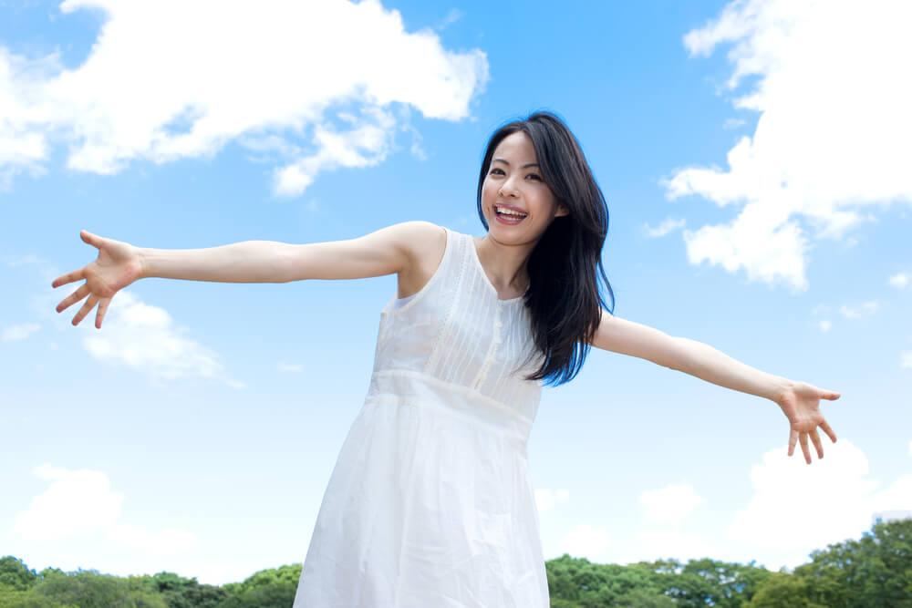 清潔感ある真っ白なワンピースを着て両手を広げたアジア人女性